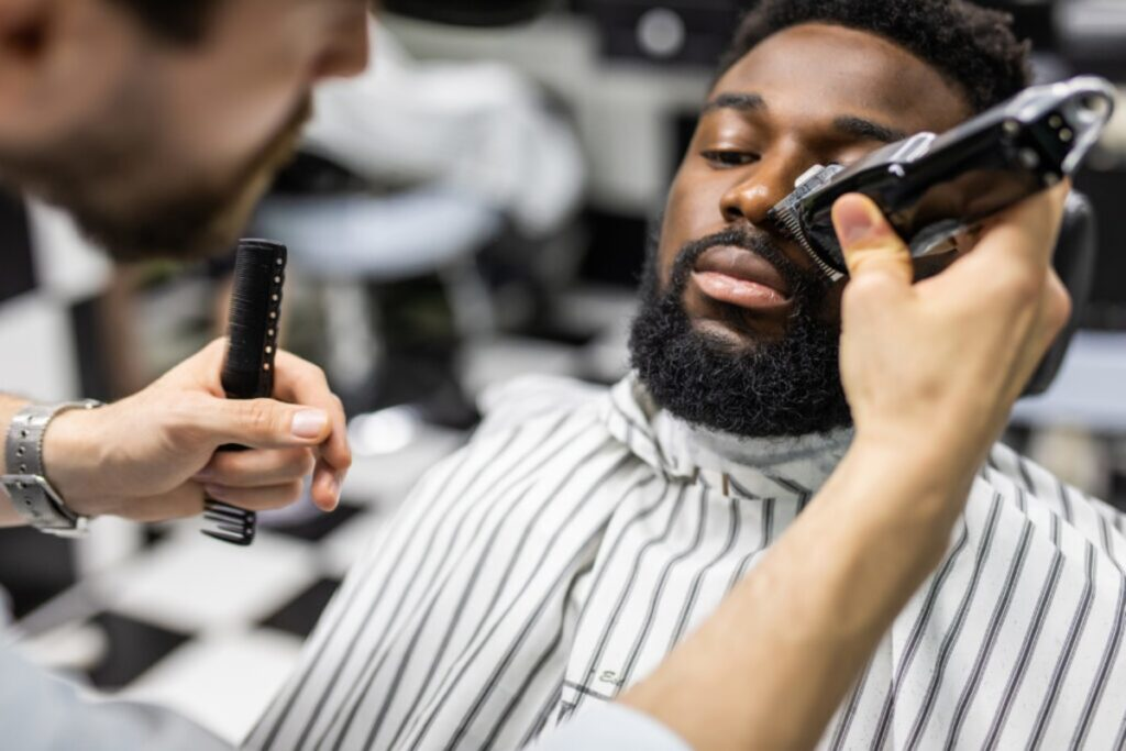 Barber using the best beard trimmer on a black man