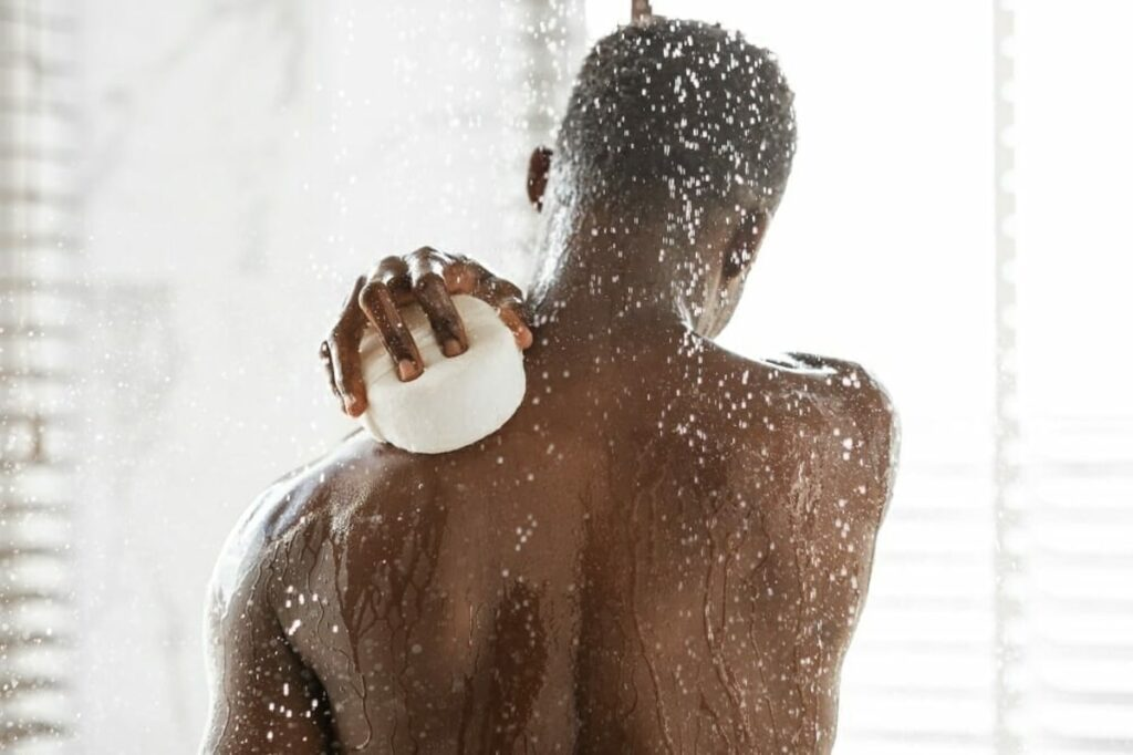 Black man using the best soap to wash his back in the bathroom