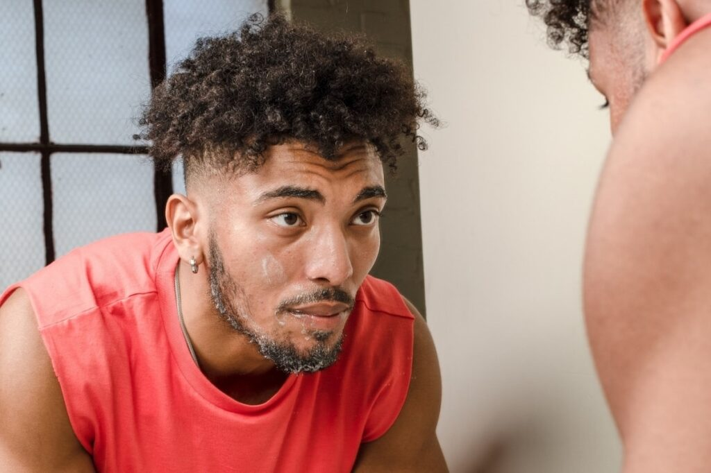 black man looking in the mirror while using a facial cleanser