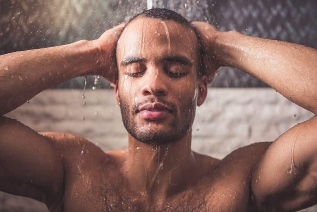 African American rinsing off the best face wash in the shower